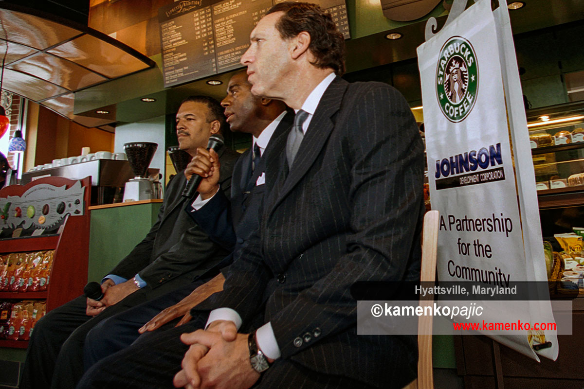 Ken Lombard, President of Johnson Development Corporation (left) and Howard Schultz, chairman and CEO of Starbucks Coffee Company (right) listen to NBA great, Earvin Magic Johnson