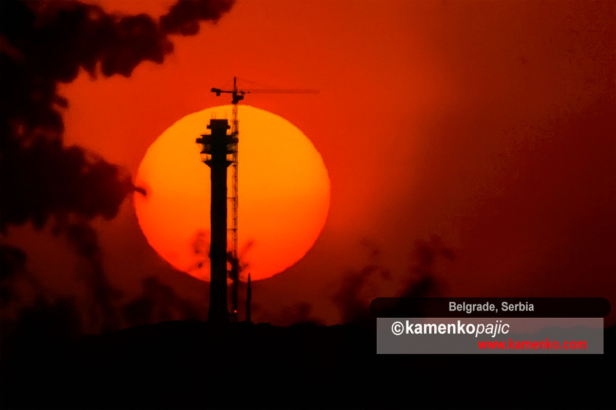 Sun rises behind silhouette of TV tower