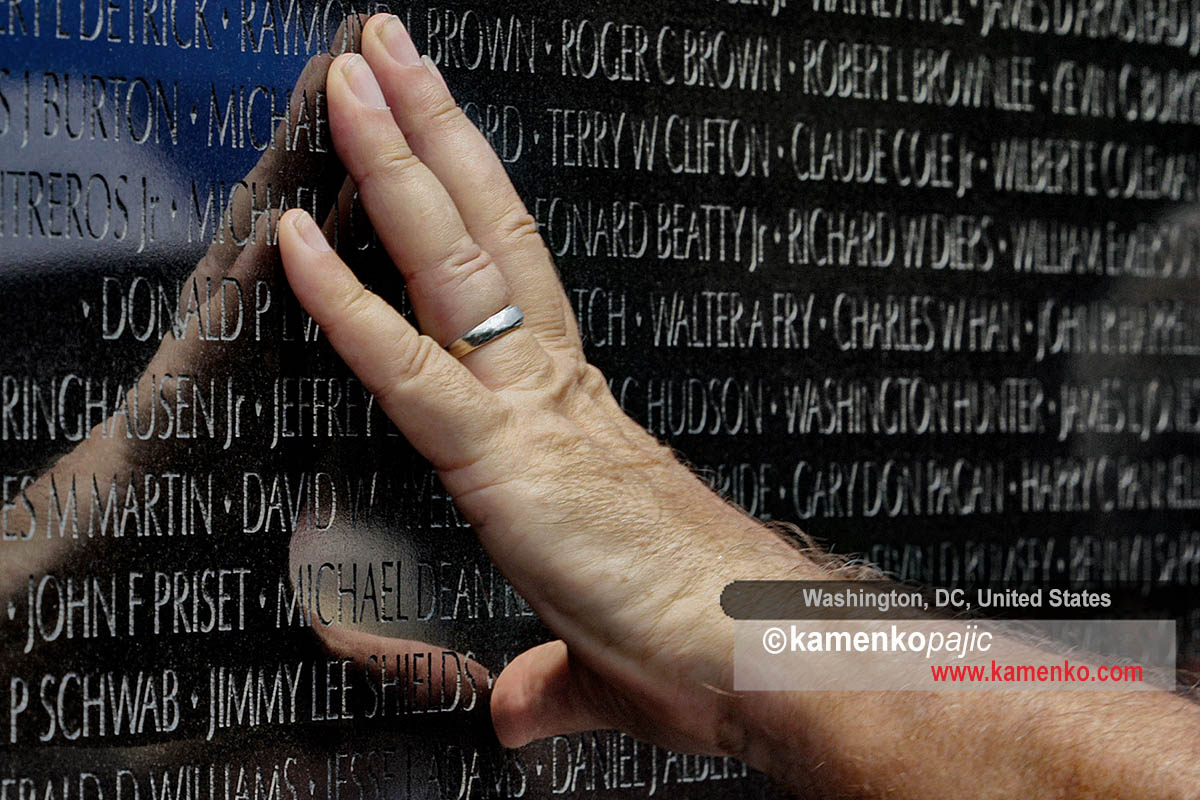 A visitor touches the Vietnam Memorial Wall