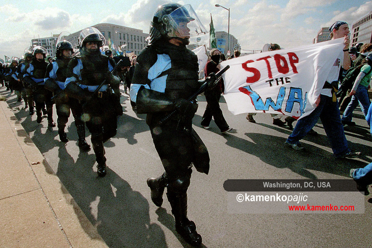 Police officers follow demonstrators during a rally against the World Bank and the International Monetary Fund in Washington