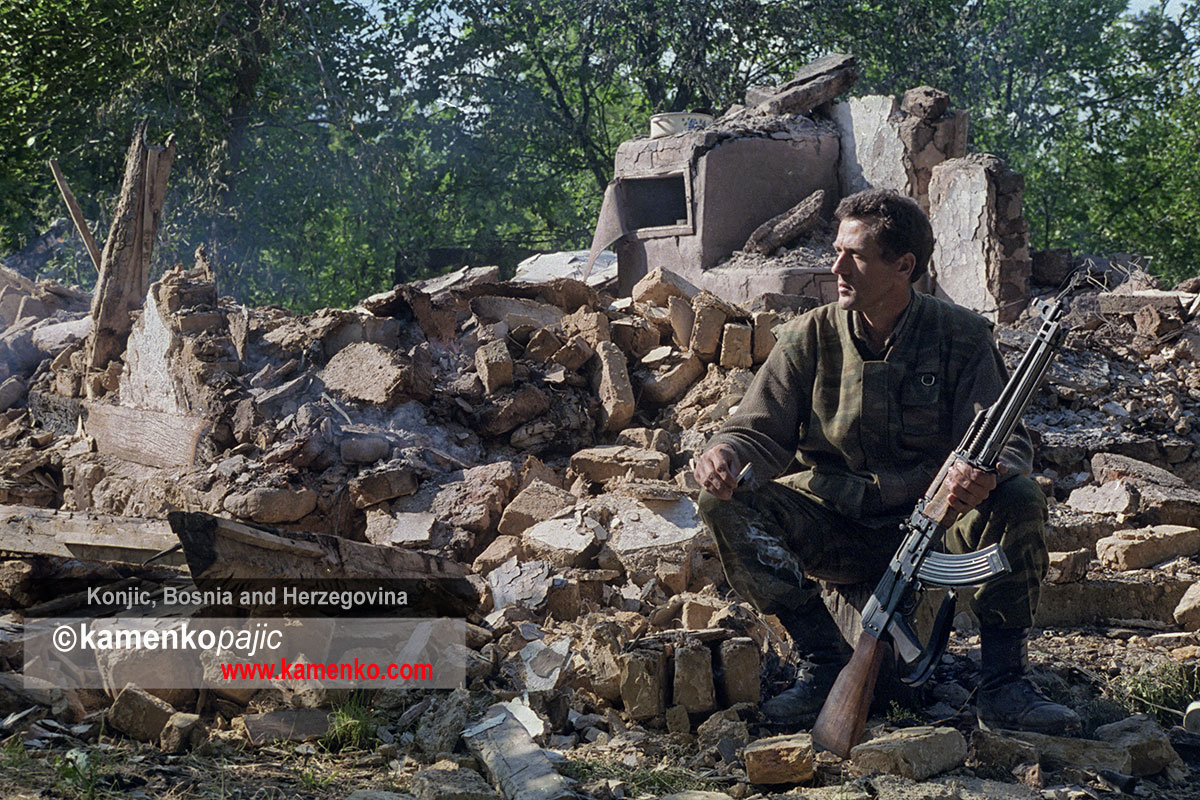 A Bosnian Serb soldier sits among the remians of his home destroyed in a Bosnian Moslem Forces raid