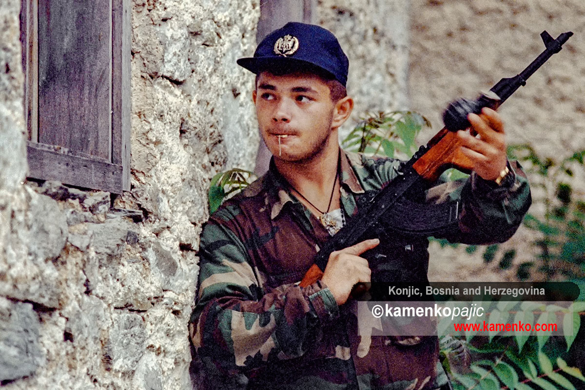 Bosnian Serb soldier throws a hand grenade
